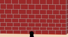 A young girl faces a tall brick wall.