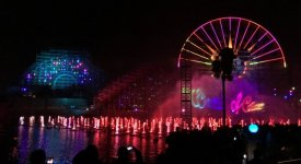 Fountains colored by light and a glowing ferris wheel mark the nighttime scene.